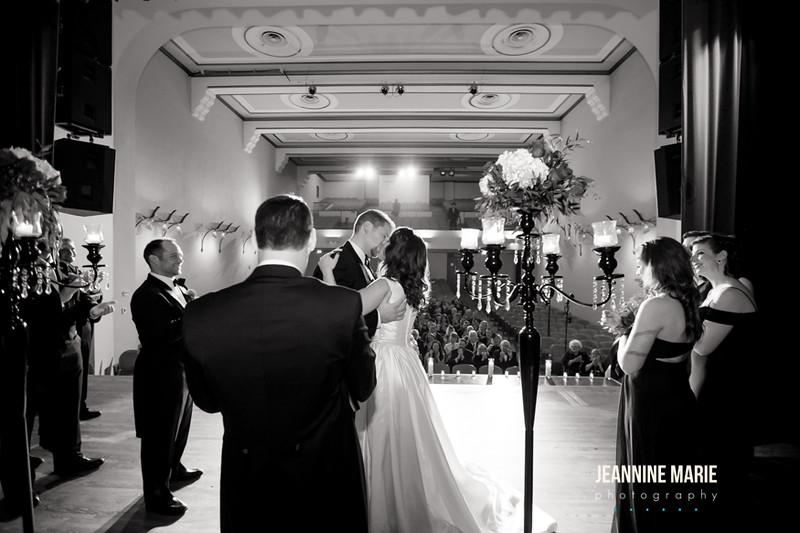The first kiss of husband and wife in black and white shot from behind towards guests overseeing tall candleabras with crystals and flowers and candles