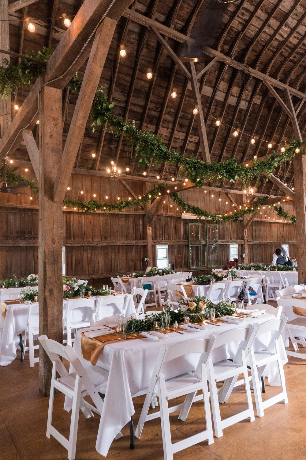 Minnesota wedding reception inside a barn with decor rentals like gold table runners, white linens, garland, and cafe lighting
