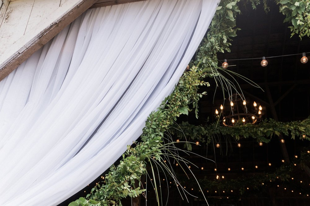 upclose curtains and garland with a chandelier and cafe lights in the background