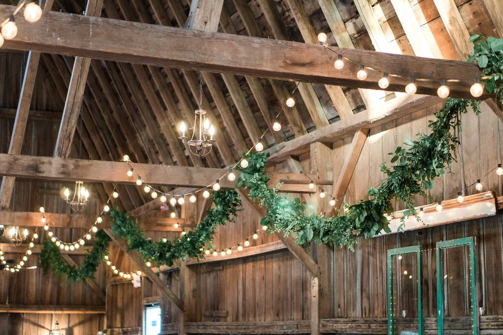 Garland and cafe lights strung from beams in a Minnesota barn for a wedding reception