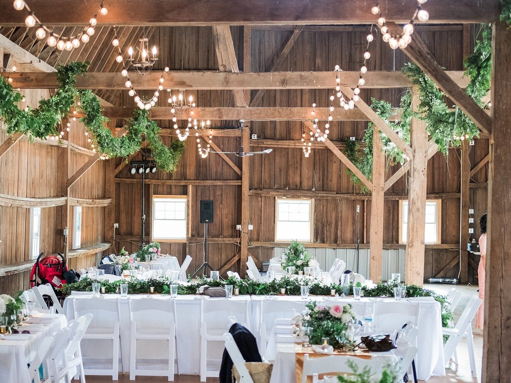 wedding barn reception with white table linens and chairs, garland hanging from the barn beams and cafe lights in between the garland