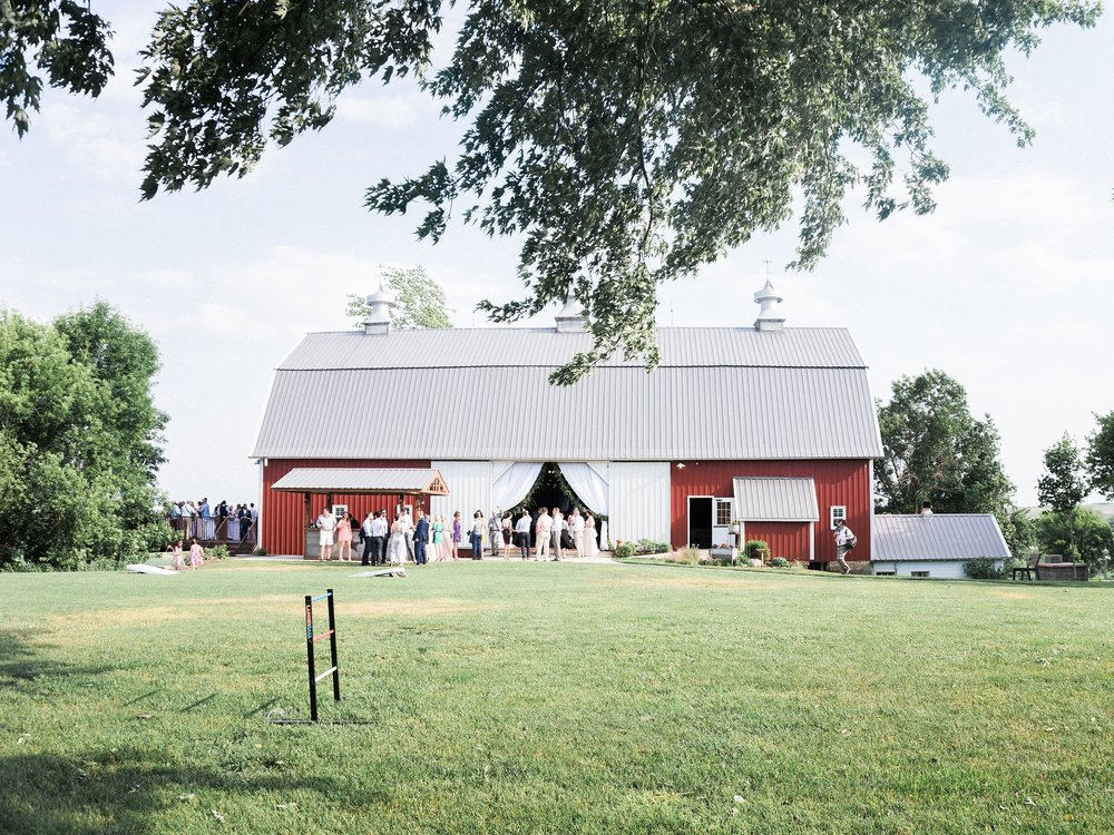 Red barn farm wedding venue with decor rentals including draping the entrance, table linens, table runners, garland and cafe lighting