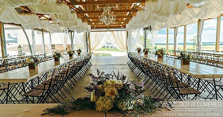 Wedding reception draping in an outside pavilion with flowers in wood boxes for the centerpiece