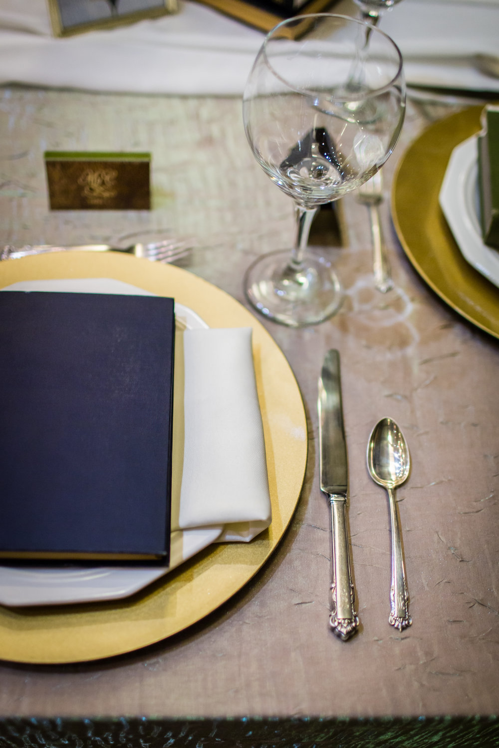 Decor for a literary themed wedding including books, gold chargers, ivory napkins, and a textured linen
