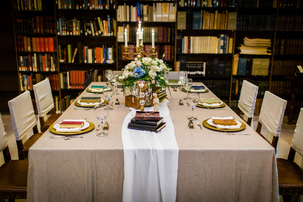 Minnesota Wedding head table pictured with books for decor along with gold plates, textured table cloth, chiffon runner and wood floral boxes