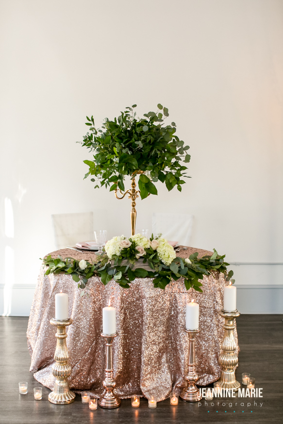 Sweetheart table with gold candelabra holding greenery arrangement. Romantic candles placed nearby.