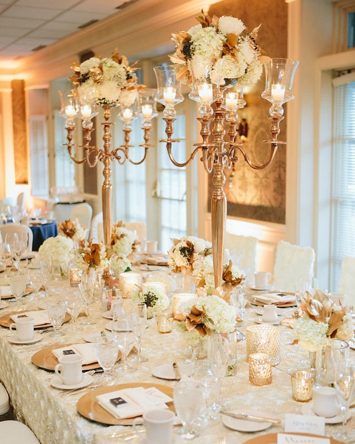 Gold candelabras holding flower and candles. Displayed on top of a rosette linen and gold chargers with candle votives nearby.