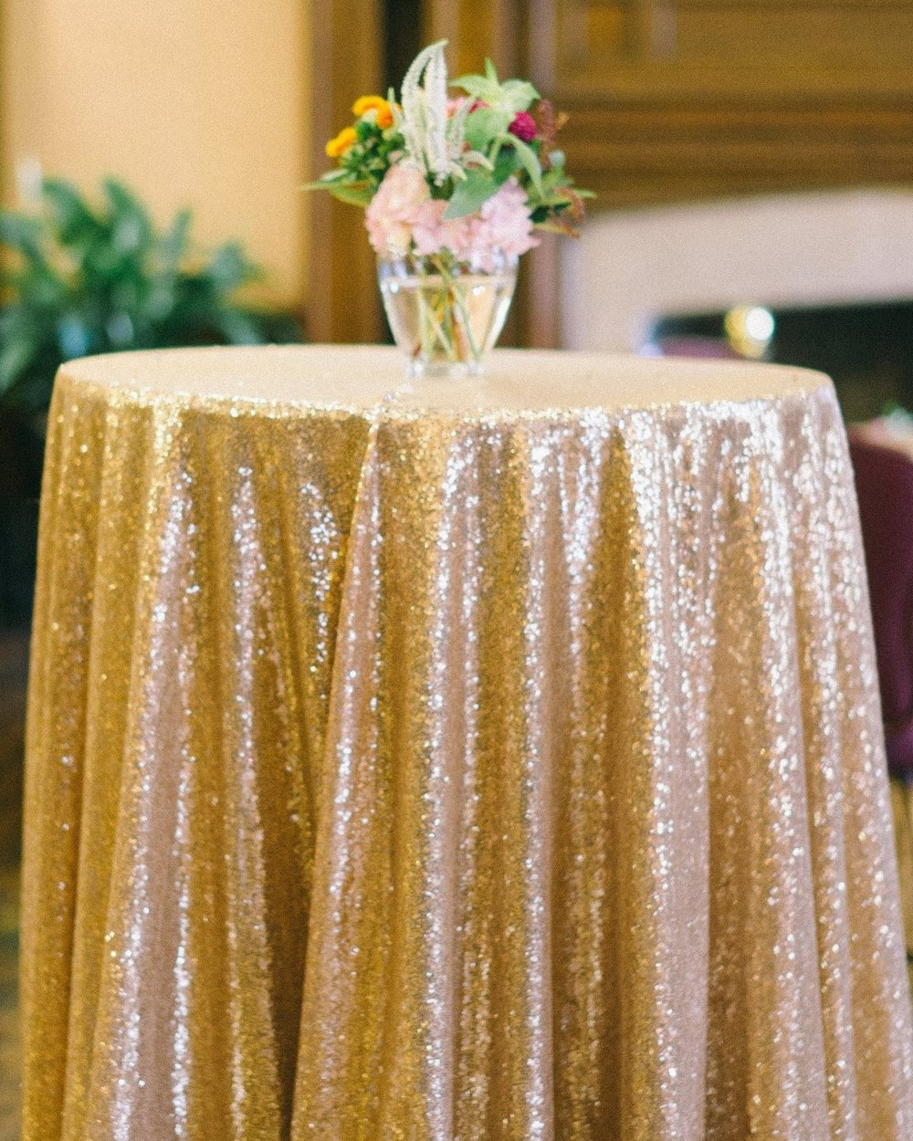 Gold sequin table linen with flowers on top