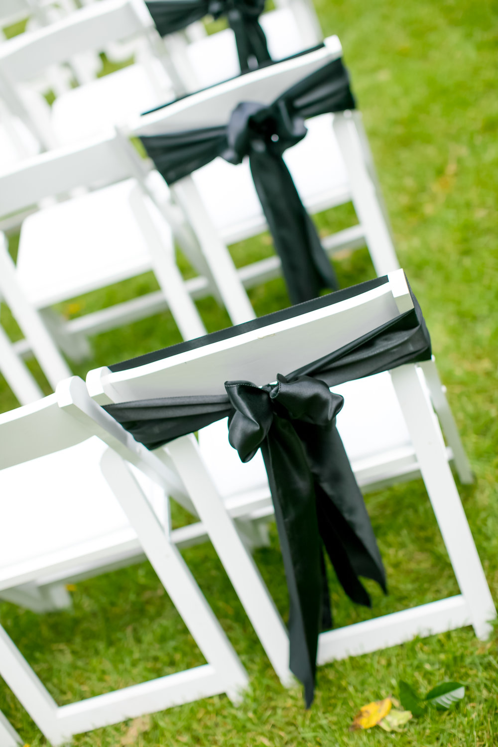 Black chair sash tied in a bow at a Minnesota outdoor wedding ceremony site.