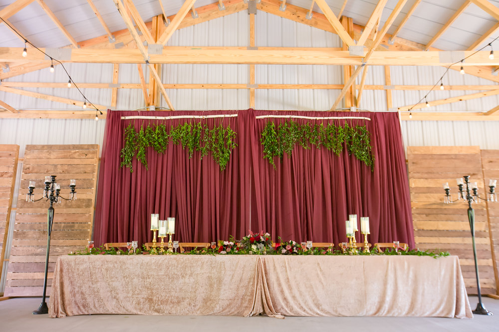 Full head table design displaying a burgundy backdrop with hanging greenery. On the table is a velvet linen and garland lining the length with gold accented candles. Next to the table are tall black candelabras for added glam.