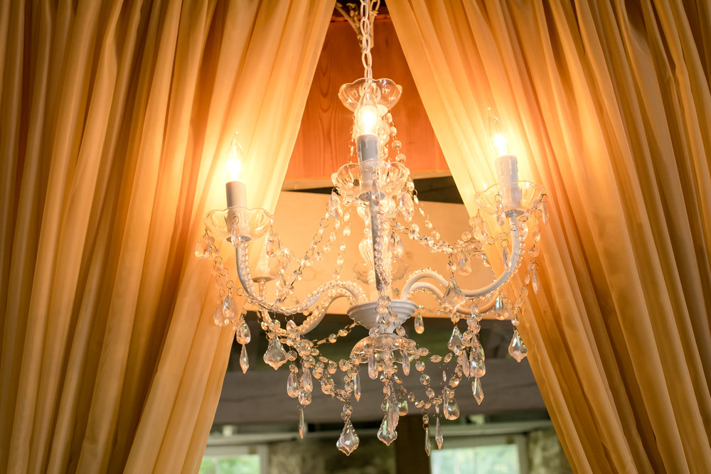 crystal chandelier on a taupe curtain backdrop