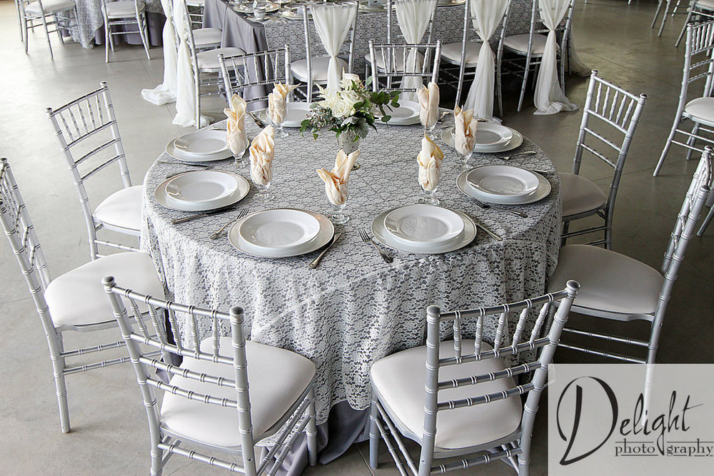 reception table styled with grey linens and lace overlays. The ivory napkins placed in glasses and a floral arrangement for a centerpiece