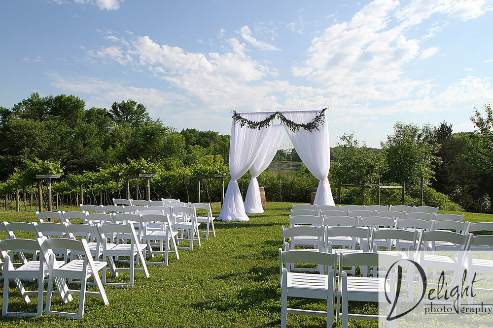 Outdoor wedding ceremony leading to a white curtain pergola with garland