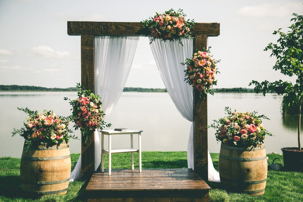 Soft white draping on the ceremony arch near lakefront decorated with flowers and whiskey barrels.