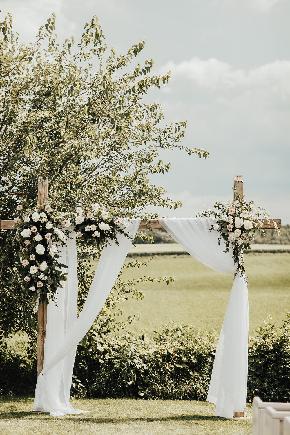 Summer wedding with draping on the ceremony arch and flower arrangements attached