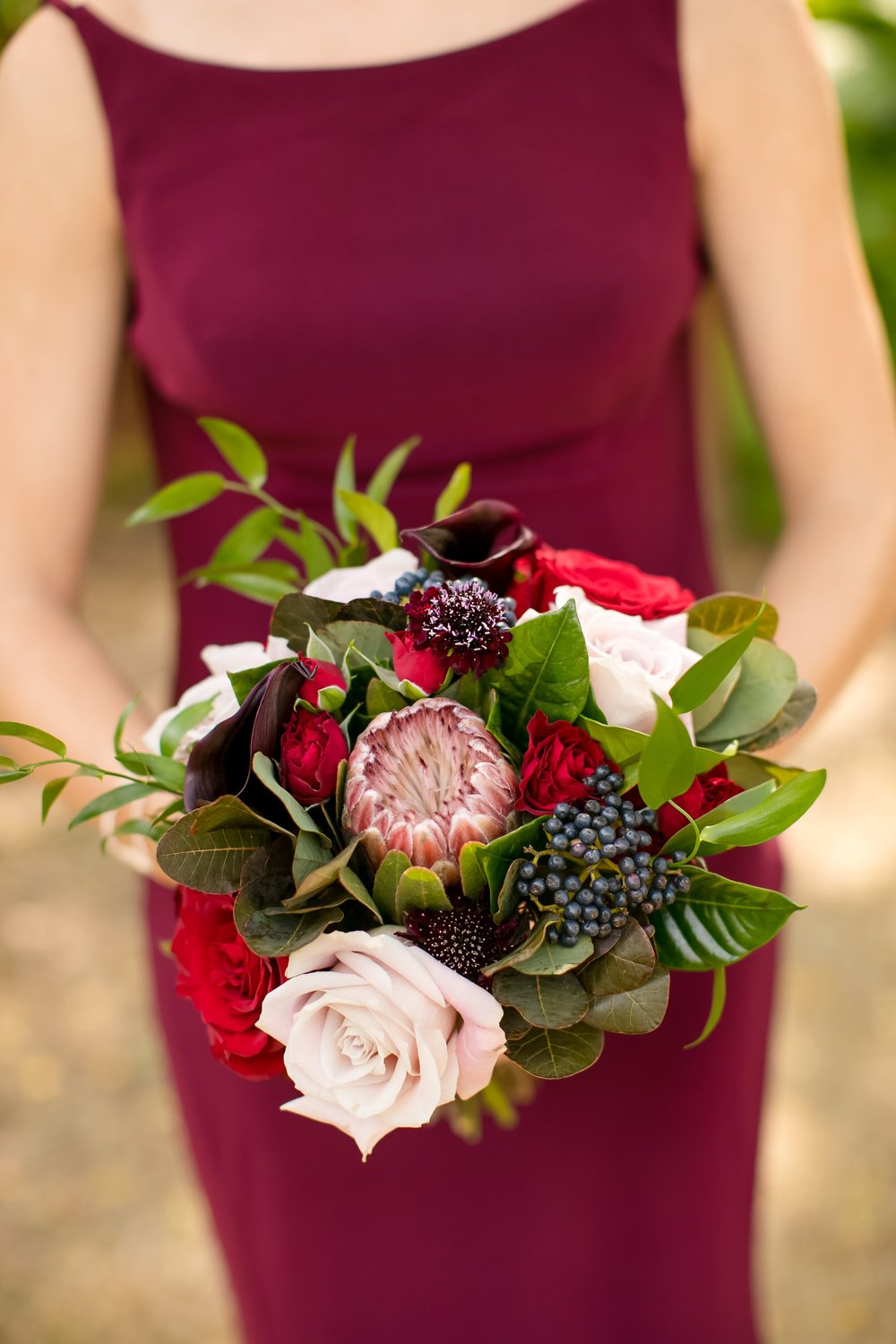 Bridesmaid in burgundy dress holding flower bouquet