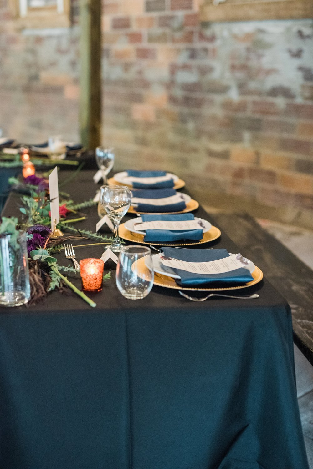 black linen head table with gold chargers and navy napkins