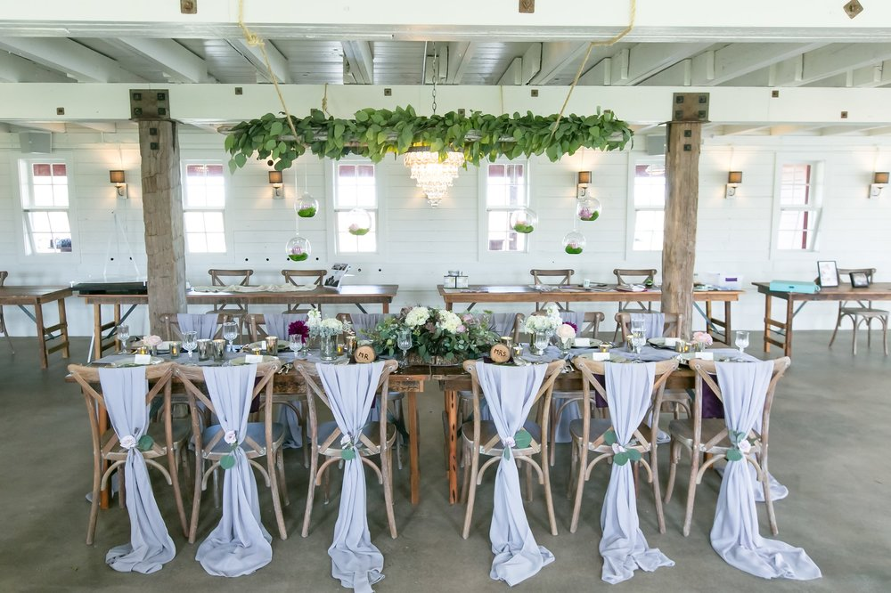 harvest table with grey chiffon on chairs and hanging greenery above table