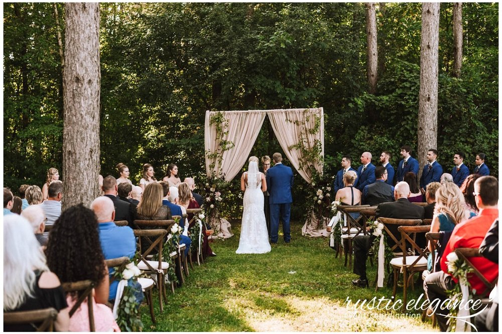 taupe backdrop with greenery for a wedding ceremony in the woods