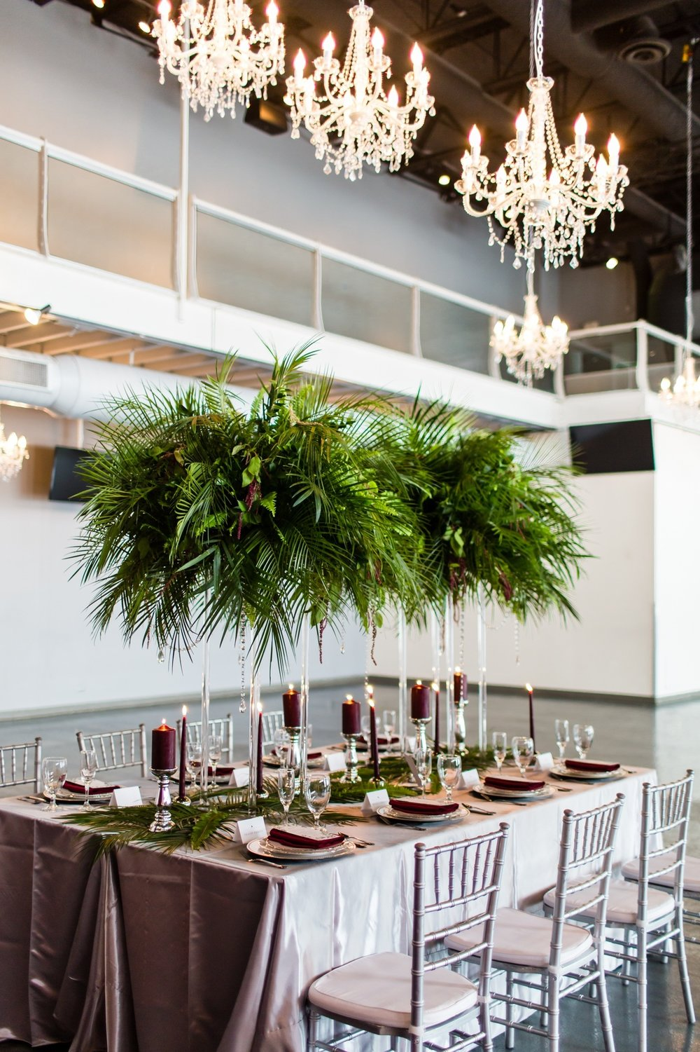 head table under three chandeliers with rented linens and napkins