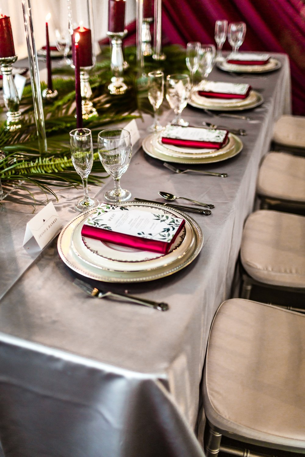 Silver linen with burgundy napkin displayed on head table