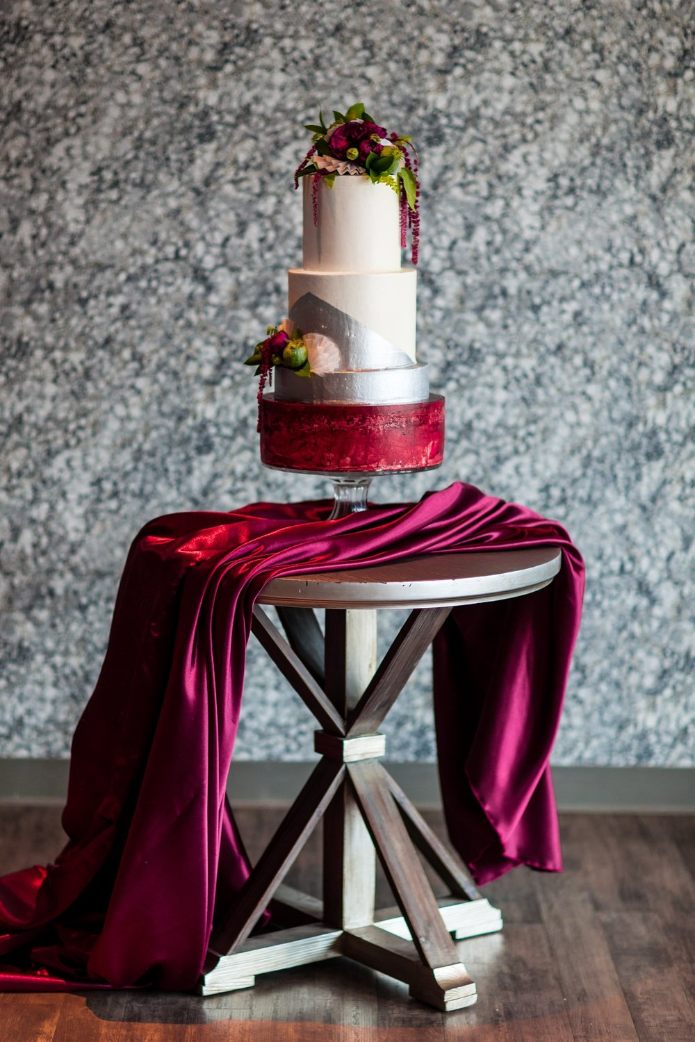 wedding cake with burgundy linen draped over table