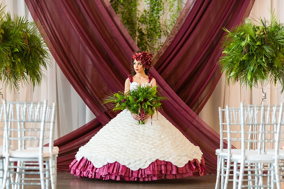 Paper dress being modeled in front of white and burgundy backdrop