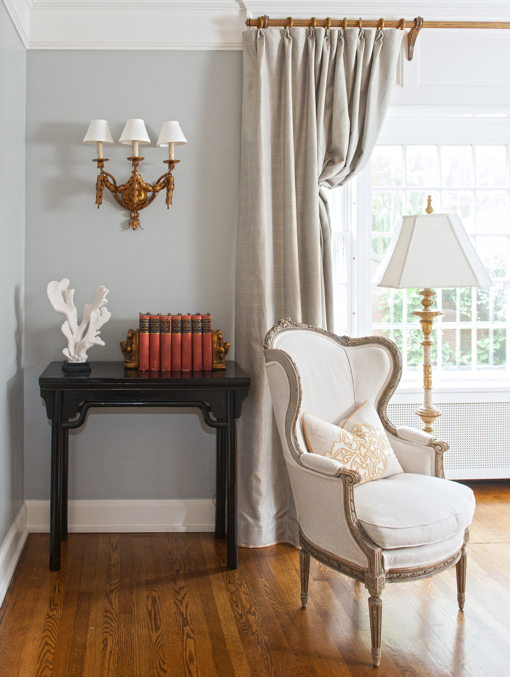 traditional interior design living room brass sconce grey window treatments