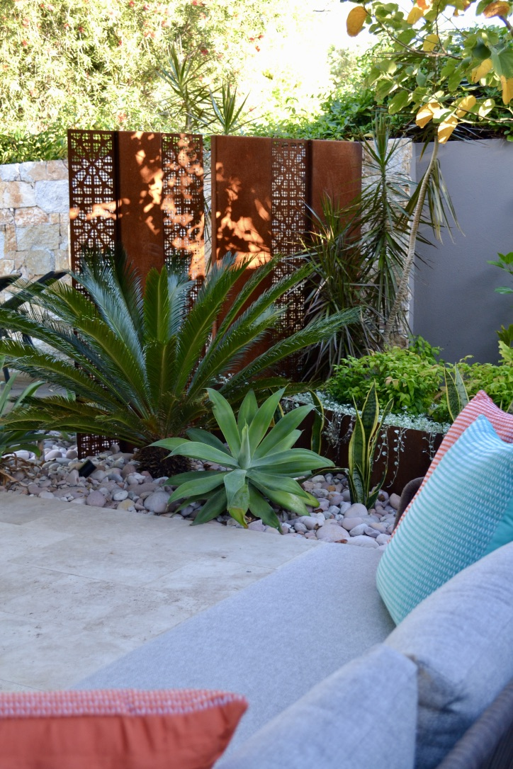 A comfortable outdoor lounge with colourful scatter cushions, travertine pavers, river stones, a corten steel screen and curved raised planter, surrounded by mixed low maintenance plantings.