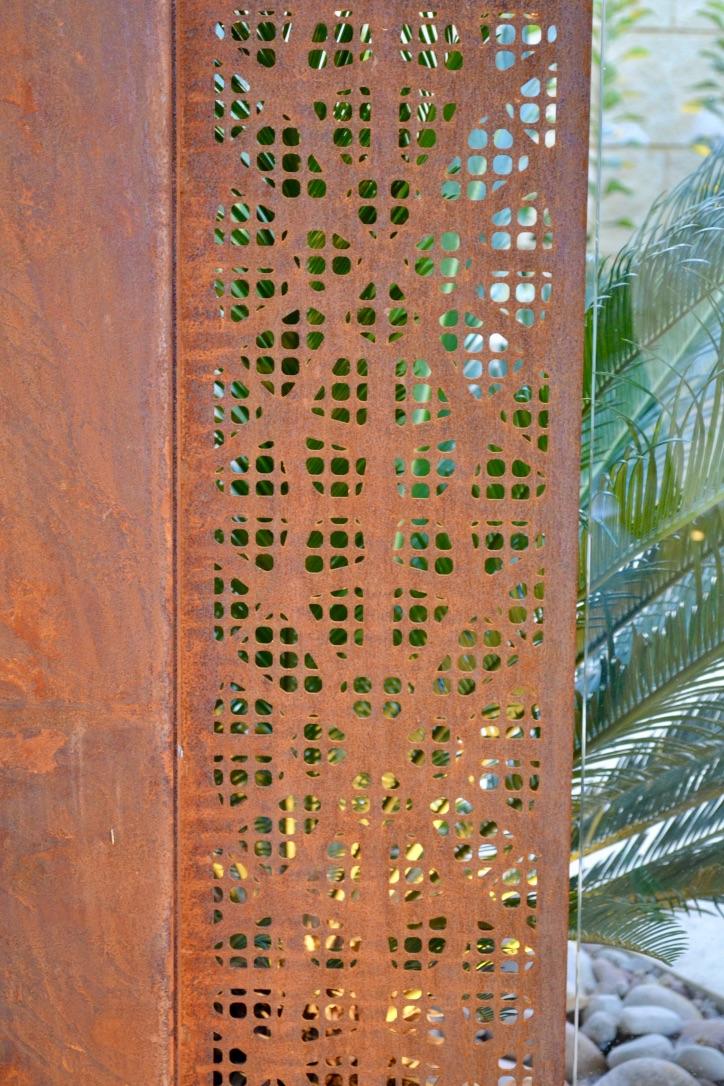 A decorative corten steel screen provides a unique pool fence solution.