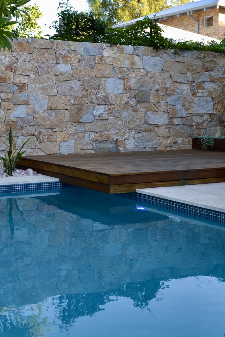 A Coolum Random Ashlar stone wall, with a spotted gum timber sun lounge deck overhanging the crystal clear swimming pool.