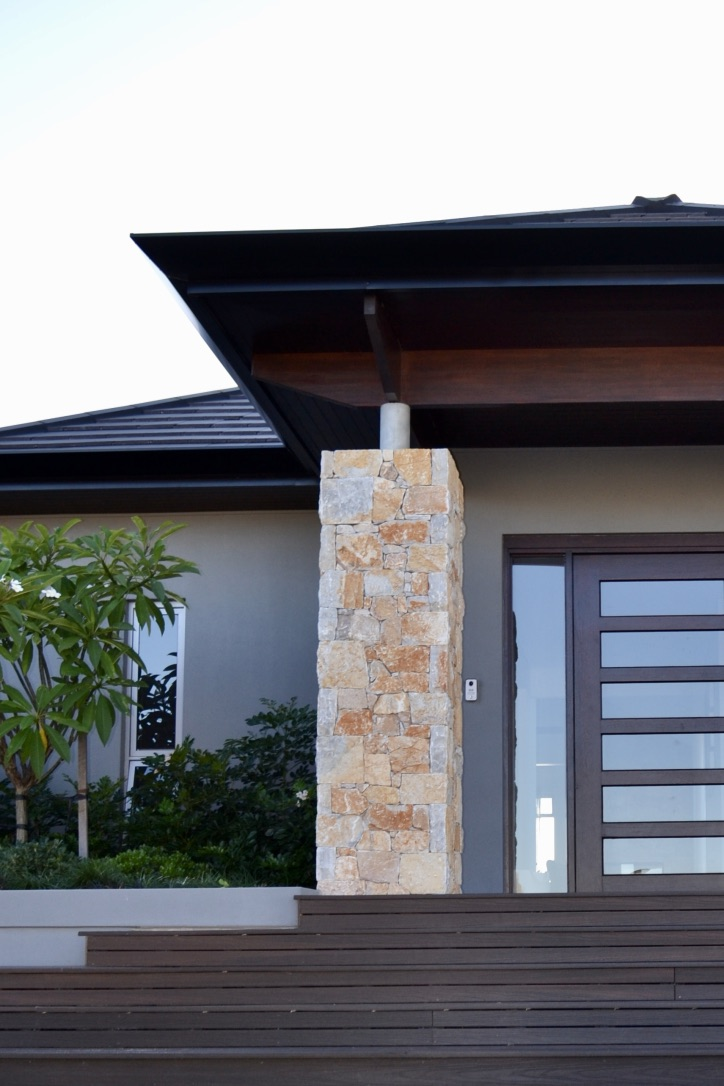 Composite timber steps lead up to the entrance of this contemporary home, with Coolum Random Ashlar stone feature pillars and a lush layered plant palette.