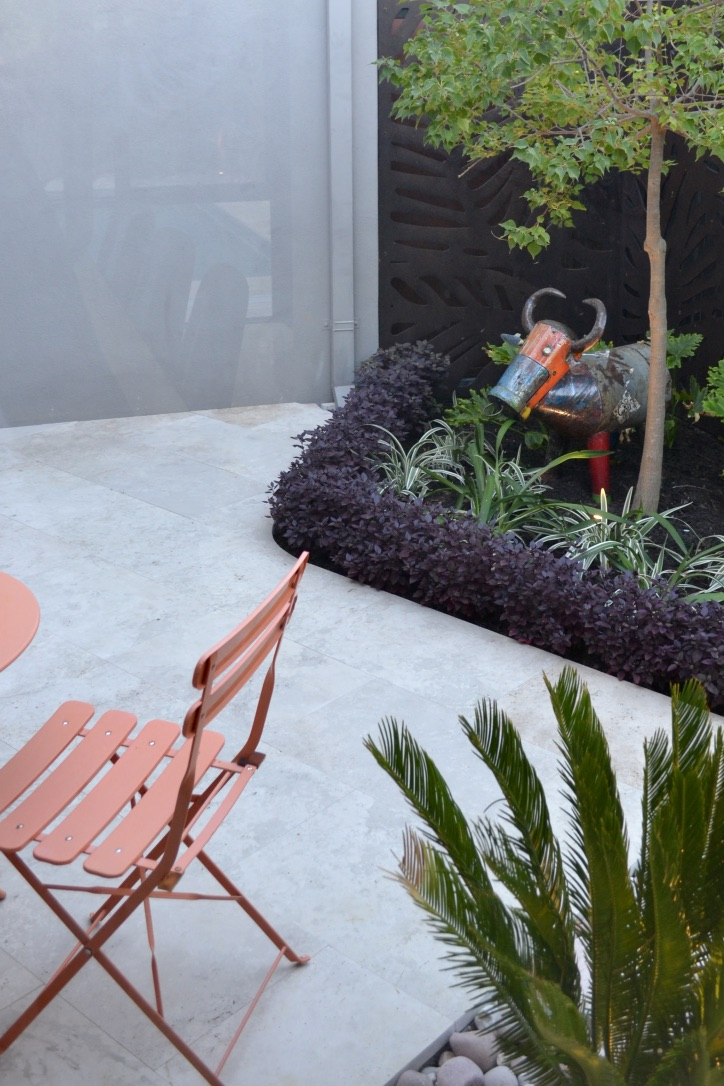 A view of a small urban courtyard, which includes a fun sculptural element, river stones, travertine, outdoor table and chairs, a curved planter with layered plantings and Outdeco screens.