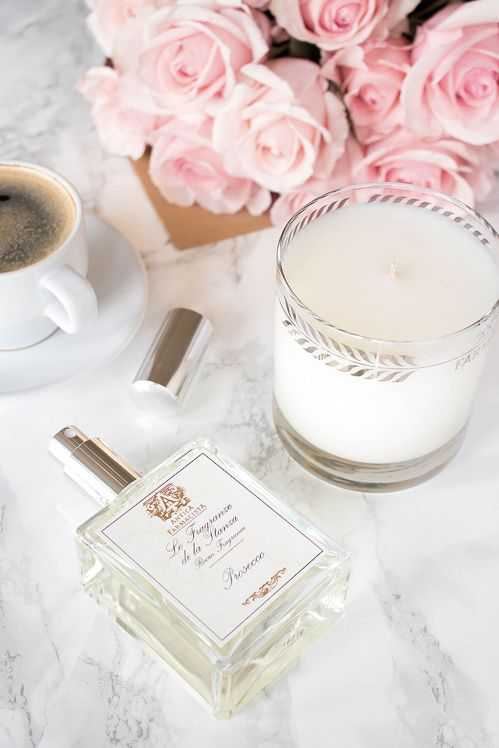 Effortlessly transition into spring with these 5 accessories and scents to try this spring season featuring Antica Farmacista Platinum Round White Candle and Antica Farmacista Room and Linen Spray with pink roses, espresso, and matches
