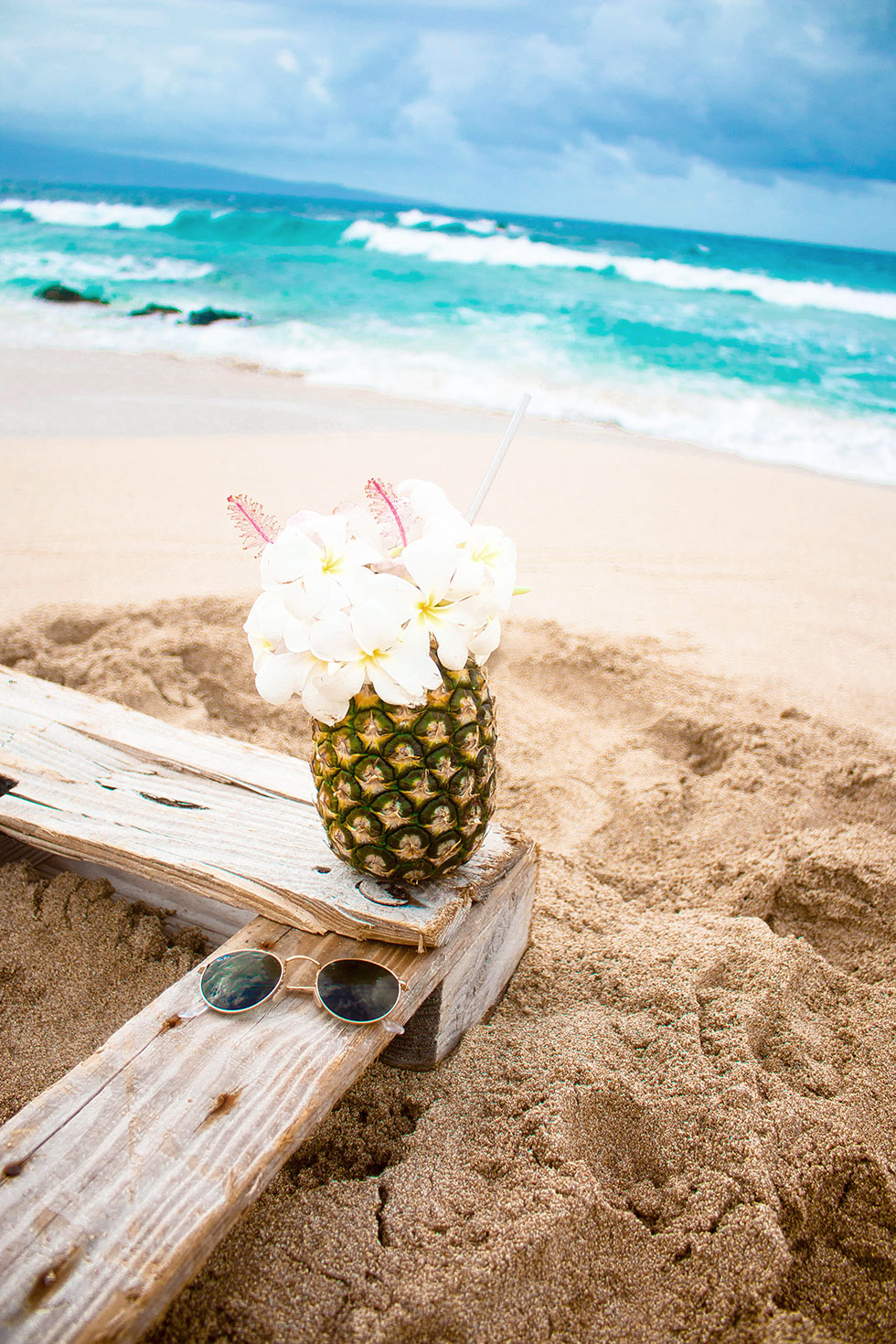 pineapple cocktail withe flowers on the beach maui