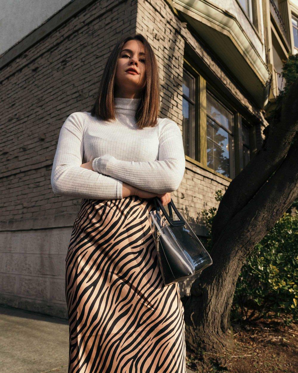 Sarah Butler of Sarah Styles Seattle wears Club Monaco Julie Rib Turtleneck Sweater, Tiger Print Midi Skirt, and Staud Mini Shirley Transparent Handbag | @sarahchristine1.jpg