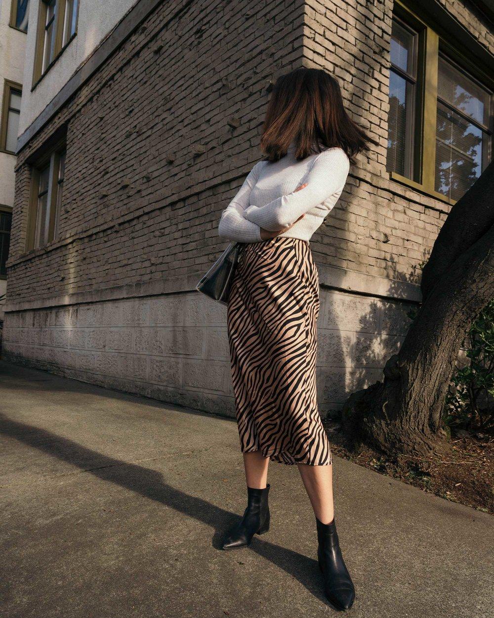 Sarah Butler of Sarah Styles Seattle wears Club Monaco Julie Rib Turtleneck Sweater, Tiger Print Midi Skirt, and Staud Mini Shirley Transparent Handbag | @sarahchristine7.jpg