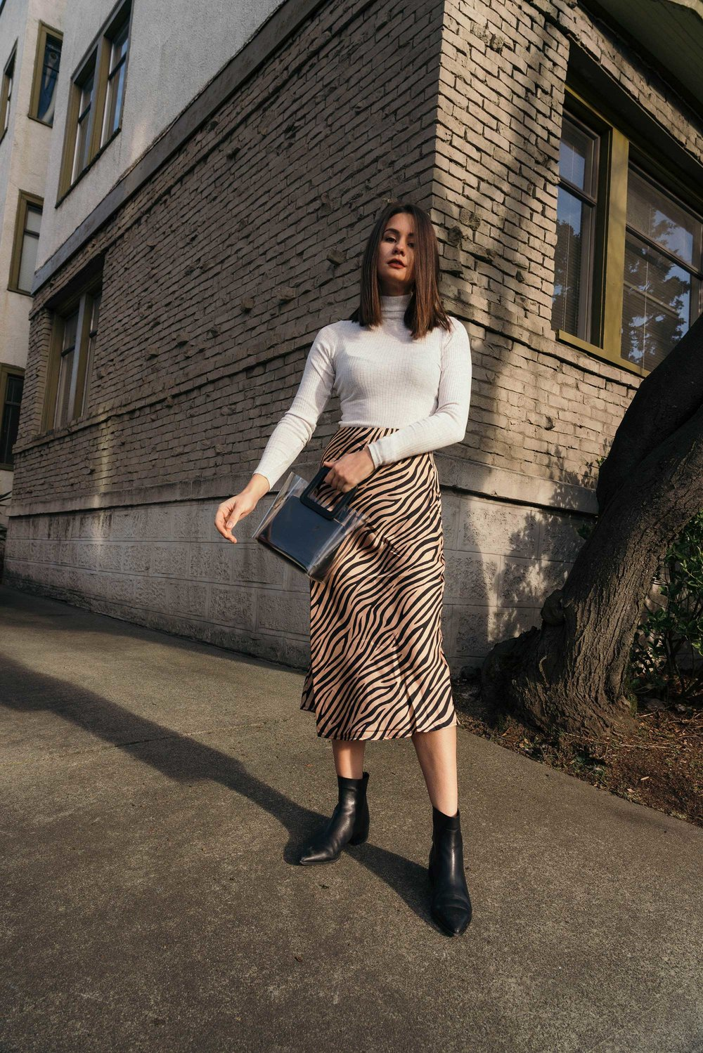 Sarah Butler of Sarah Styles Seattle wears Club Monaco Julie Rib Turtleneck Sweater, Tiger Print Midi Skirt, and Staud Mini Shirley Transparent Handbag | @sarahchristine8.jpg