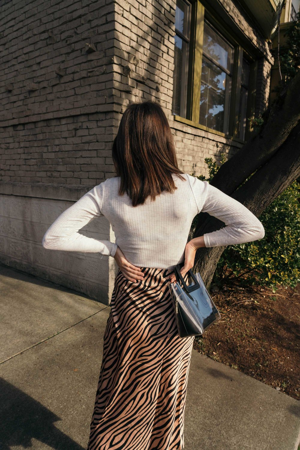 Sarah Butler of Sarah Styles Seattle wears Club Monaco Julie Rib Turtleneck Sweater, Tiger Print Midi Skirt, and Staud Mini Shirley Transparent Handbag | @sarahchristine4.jpg