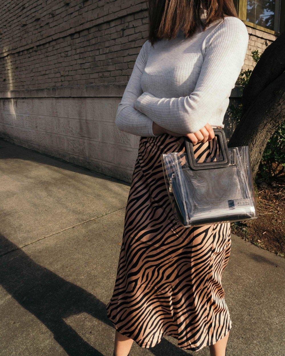 Sarah Butler of Sarah Styles Seattle wears Club Monaco Julie Rib Turtleneck Sweater, Tiger Print Midi Skirt, and Staud Mini Shirley Transparent Handbag | @sarahchristine2.jpg