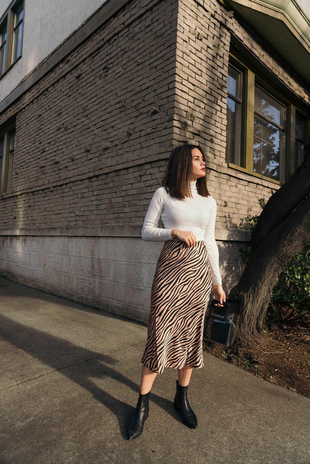 Sarah Butler of Sarah Styles Seattle wears Club Monaco Julie Rib Turtleneck Sweater, Tiger Print Midi Skirt, and Staud Mini Shirley Transparent Handbag | @sarahchristine.jpg