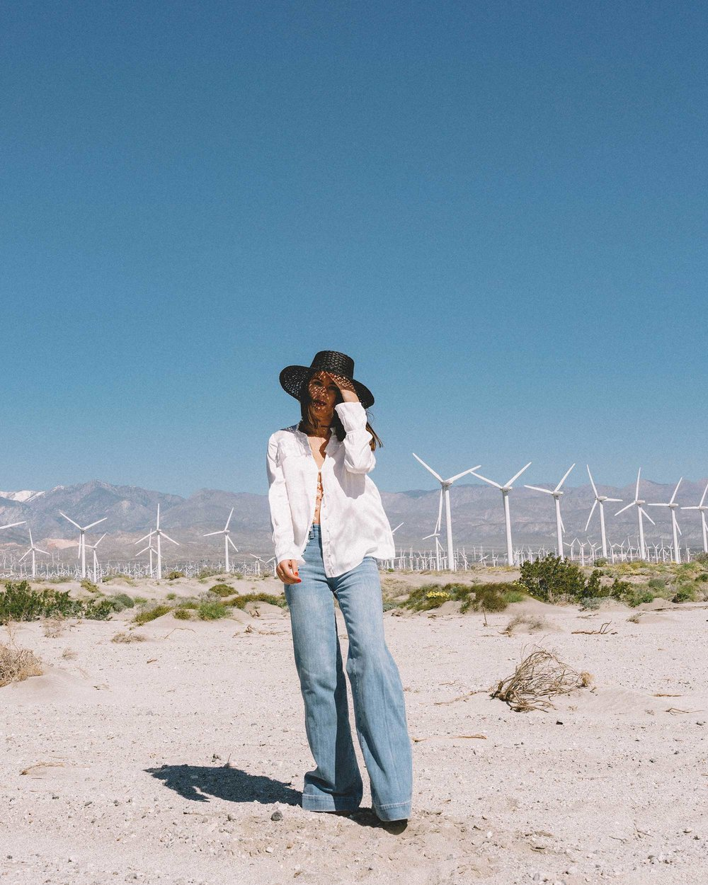 Sarah Butler of Sarah Styles Seattle wears Paige Anguilla Long-Sleeve Blouse with Layered Ruffle Trim, Paige Sutton High Waist Wide Leg Jeans, and Lack of Color Women's Sunnydip Noir Hat in Palm Springs for Coachella Festival Outfit   @sarahchristine4.jpg