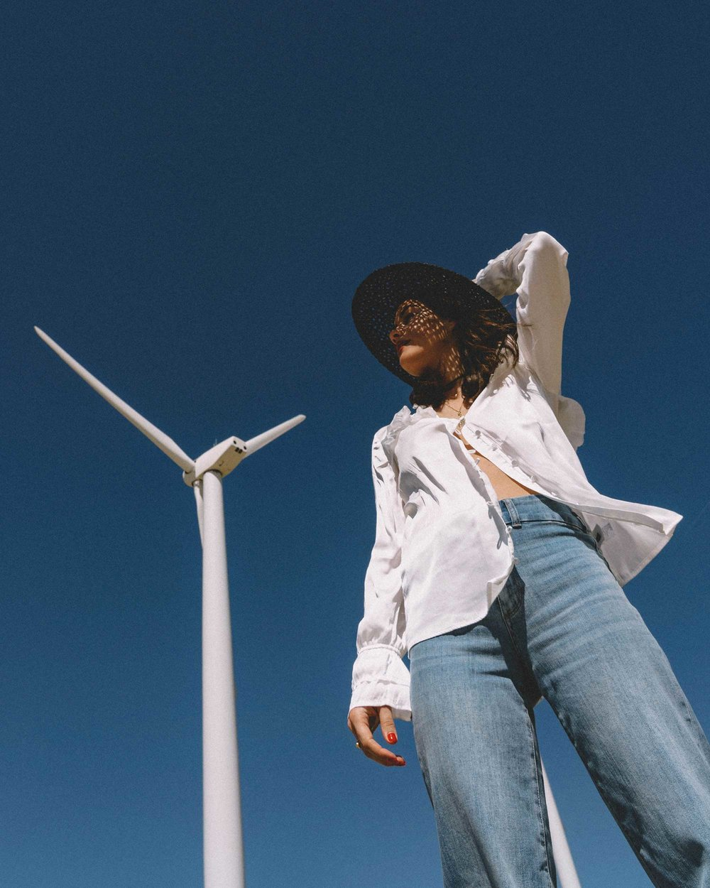 Sarah Butler of Sarah Styles Seattle wears Paige Anguilla Long-Sleeve Blouse with Layered Ruffle Trim, Paige Sutton High Waist Wide Leg Jeans, and Lack of Color Women's Sunnydip Noir Hat in Palm Springs for Coachella Festival Outfit   @sarahchristine5.jpg