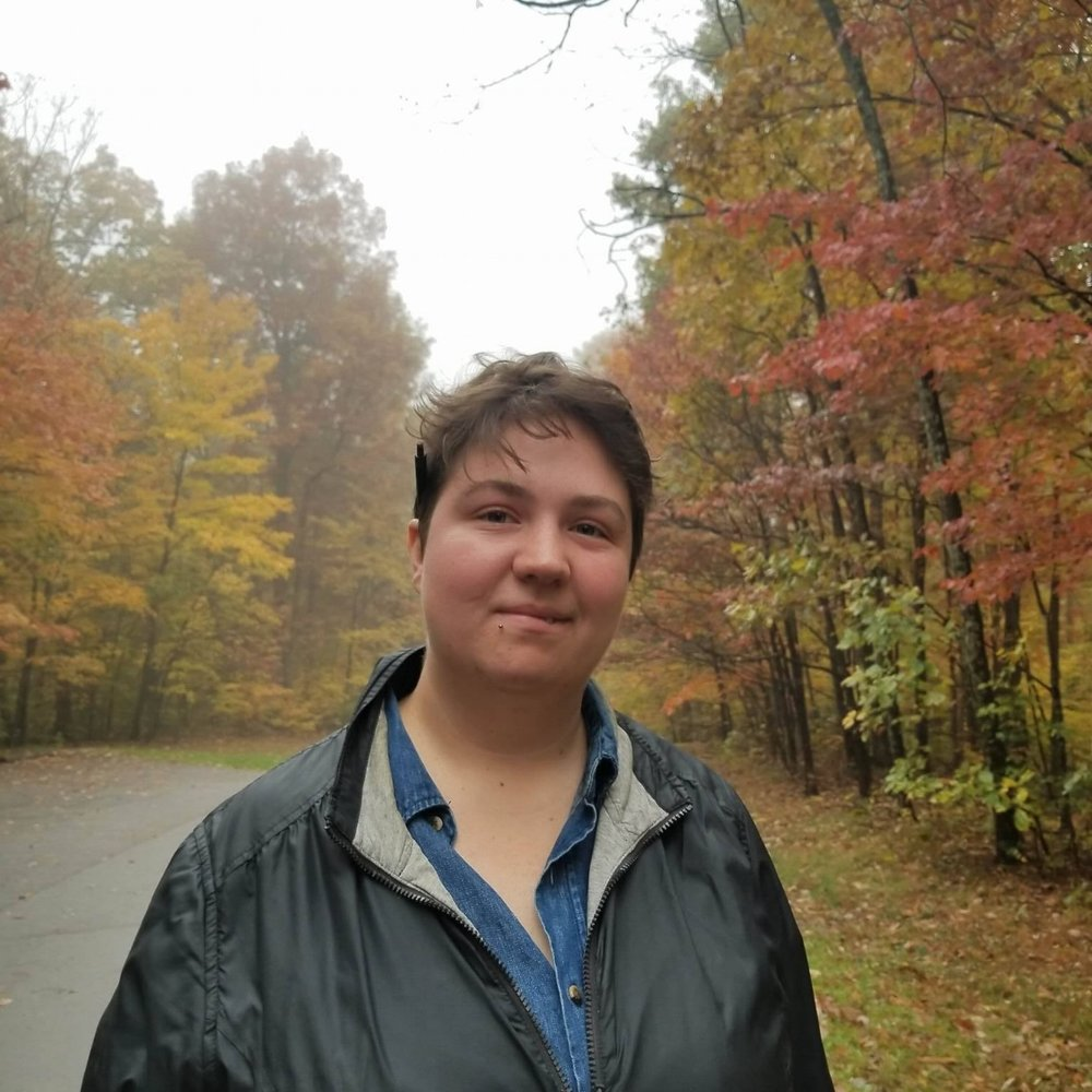 Cailin Ashbaugh - grew up in a Northwest Michigan conifer farm. Currently she works as an evening librarian, and spends her time writing on paper coffee cozies, and reading anything she can get her hands on.