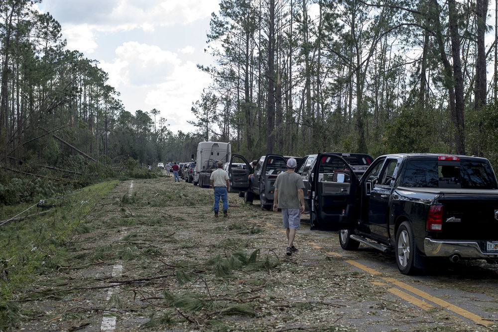 The Return - Mexico Beach area residents wait for hours to return to their homes, as clean-up crews remove trees from the road. Hurricane Michael passed through a massive pine forest with winds up to 150 mph, and toppled thousands of towering trees. The 45 mile drive from the highway to Mexico Beach took almost 8 hours.
