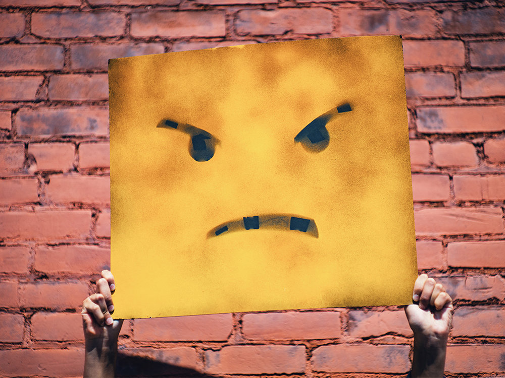 upset-smiley-face-on-poster-held-up-in-front-of-brick-wall