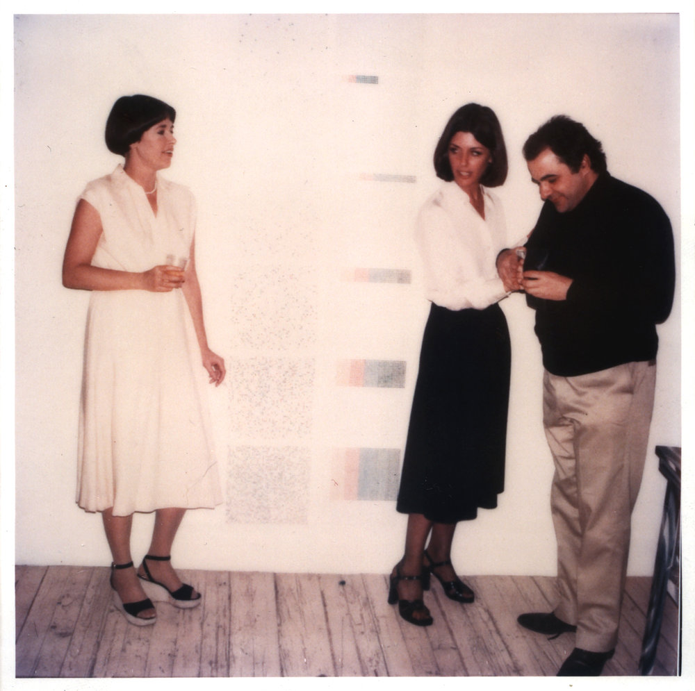 Jennifer Bartlett, Paula Cooper and Joel Shapiro at Paula Cooper's loft, circa 1980. Artwork on the wall by Jennifer Bartlett.