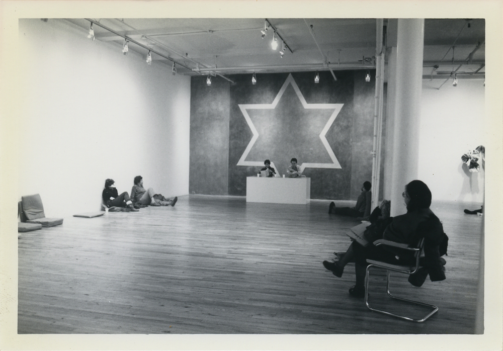"The gallery's ninth annual marathon reading of Gertrude Stein's ""The Making of Americans,"" performed at 155 Wooster Street on New Year's Eve, 1982-83. The announcement suggested, ""For your comfort bring your own cushion."" Photo by Jane Jesse Cardinale. Wall drawing by Sol LeWitt. . Sol LeWitt, ""Wall Drawing #238: Stars with three-, four-, five-, six-, seven-, eight-, nine-, ten-points, drawn with ten-inch (25 cm) wide band of yellow color ink wash. The area inside the band is red color ink wash and the area outside the band is blue color ink wash. The stars are separated by bands of India ink wash.""  First installation six-pointed star: Paula Cooper Gallery, New York, NY, December 1982 executed by: Jose Albiol, Anne Patry, Anthony Sansotta, Magdalena Zajac."