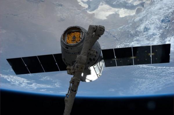 The robotic arm grapples the Dragon.Photo courtesy of NASA.