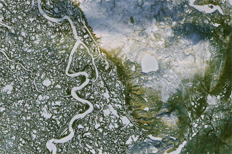 This view, acquired on Nov. 7, 2016, by Landsat 8, shows a portion of Canada's Mackenzie River Delta and the town of Inuvik, home to more than 3,000 people. A frozen highway -- 194 kilometers (120 miles) long -- runs between the remote outposts of Inuvik and Tuktoyaktuk along the river's East Channel. White, snow-and-ice covered waterways stand out amid green, pine-covered land. The low angle of the sunlight bathes the higher elevations in golden light.